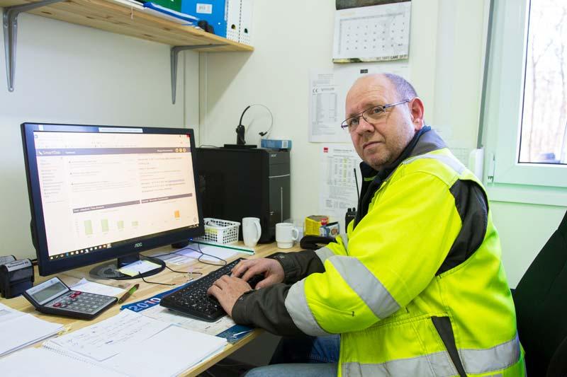 driftsjef og fagansvarlig Trond G. Furnes sitter foran datamaskinen og har full kontroll på timer og materiell gjennom SmartDok. Foto: Lasse Sørnes